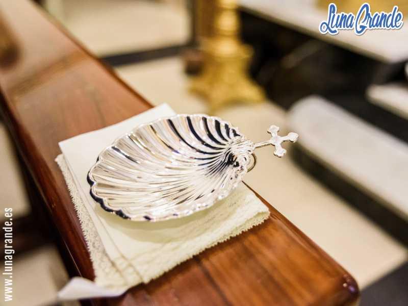 Cocha de plata para bautizo sobre el banco de una iglesia