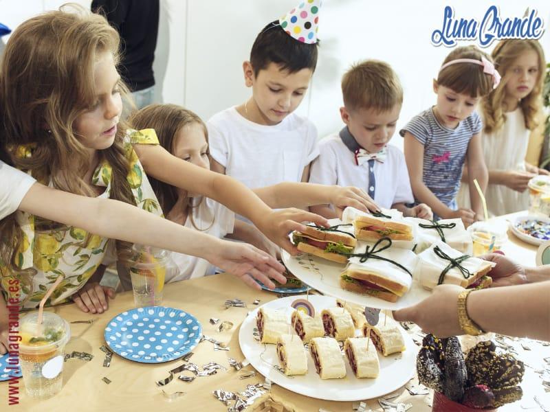 Niños comiendo sandwiches en cumpleaños infantil