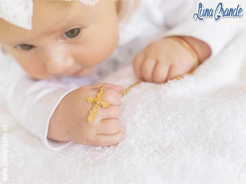 Bebé en el día de su bautizo con una cruz de oro en la mano